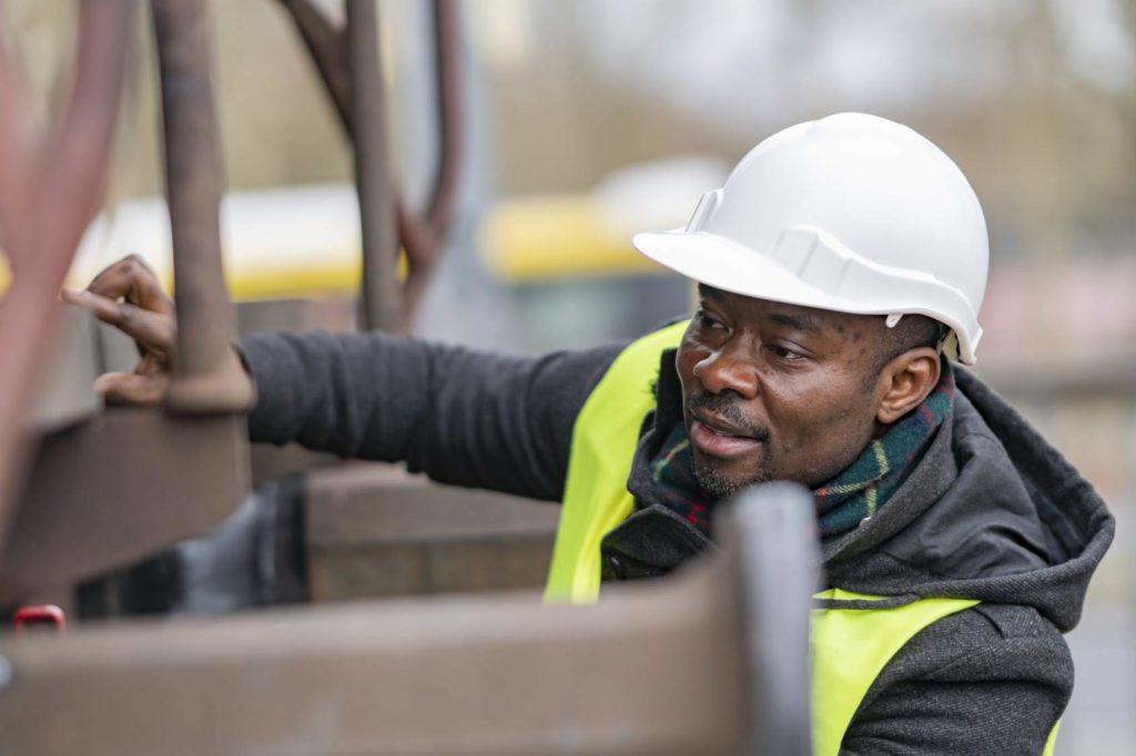 an african construction worker watching a machine